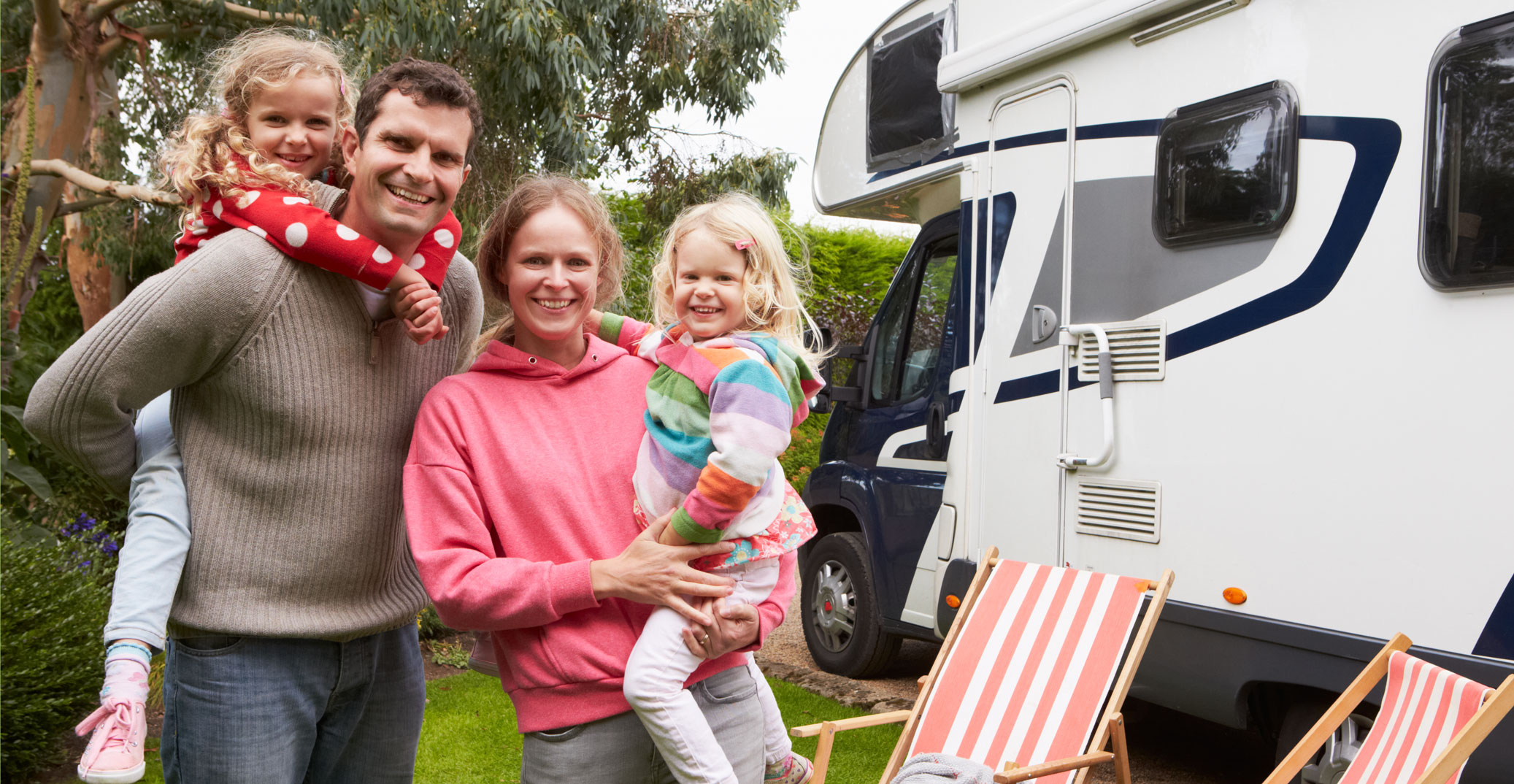 A family in front of their rental motor home