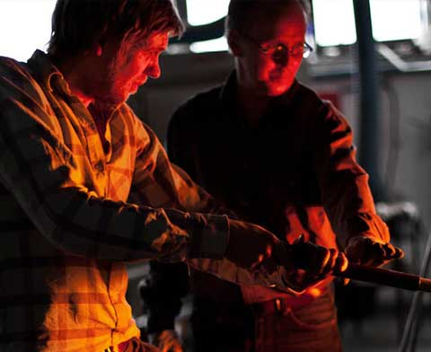 Two persons in front of a furnace working with glassblowing
