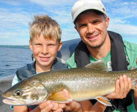 Father and son sitting in a boat holding a big fish