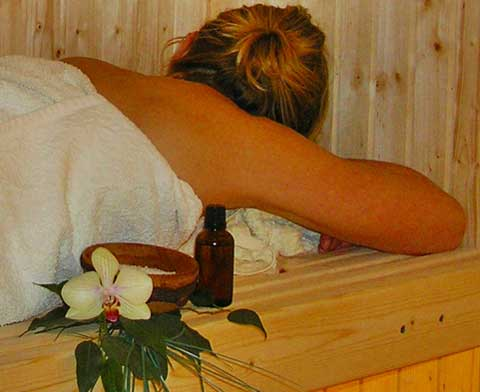 Woman on a sauna bench cover with a white bath towel