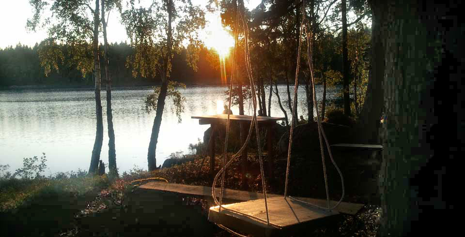 The sun is going down and shining over a lake and a swing