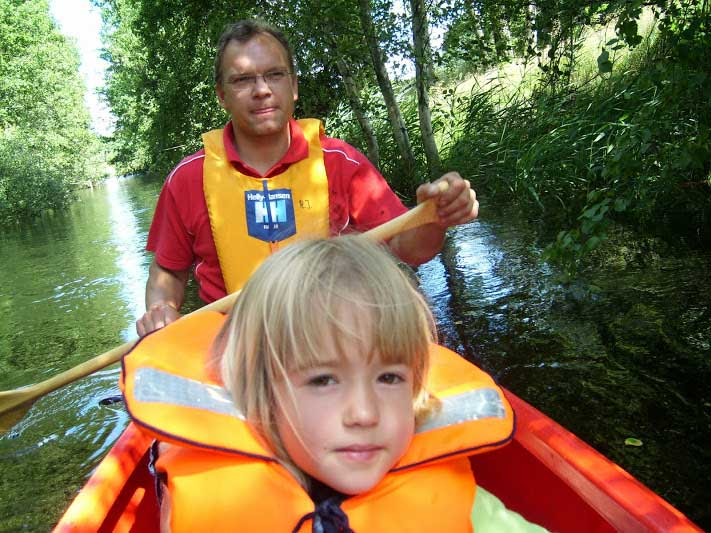 A father and his children canoeing on a river wearing yellow life jackets