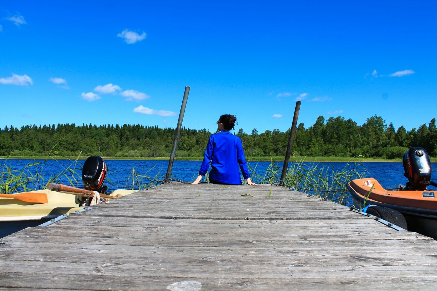 Women sitting on a jetty looking at lake
